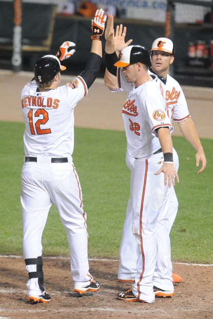 Mark Reynolds celebrates his three-run home run with Chris Davis and Matt Wieters in the sixth inning of Tuesday night's game against the Red Sox.