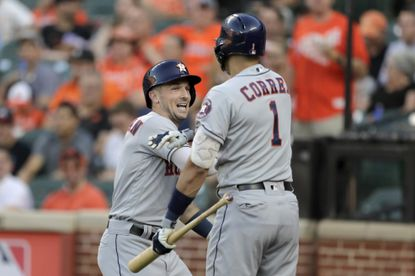 Houston Astros' Alex Bregman, left, is greeted near the dugout by Carlos Correa after hitting a two-run home run off Baltimore Orioles starting pitcher Aaron Brooks during the first inning of a baseball game Saturday, Aug. 10, 2019, in Baltimore. (AP Photo/Julio Cortez)