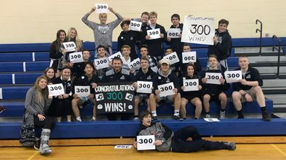 Members of the Patterson Mill wrestling team celebrate the 300th career coaching win for Huskies coach Ryan Arist during Thursday night's season-opening action.