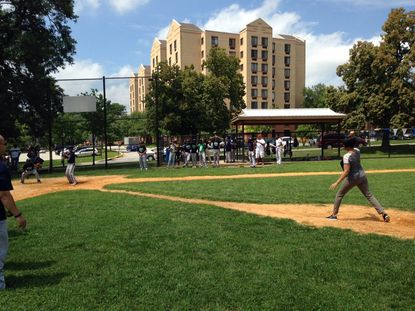 Mayor Stephanie Rawlings-Blake throws the first pitch at a community baseball game involving police and city youths on Saturday at Northwood Baseball Field. Courtesy of Marques Dent.