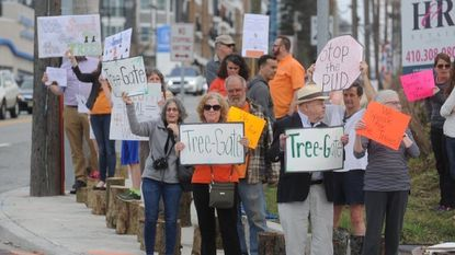 "Protesters hold signs saying ""Tree-Gate"" and ""We speak for the trees"" during a protest Wednesday evening at the intersection of York Road and Bosley Avenue in Towson."