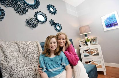 Ashley Long and her daughter, Emma, 11, sit on a marine blue crushed velvet bench in Long's office. Behind them is a mirrored wall design Long made.