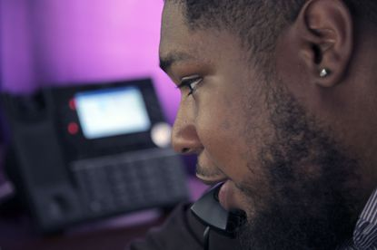 Elijah McBride, a counselor at Baltimore Crisis Response Inc., which runs the Here2Help hotline, takes calls from his workstation. He speaks to a spouse, whose partner was manic and refusing to accept help.