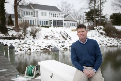 Matt Long, co-owner of Gate One Builders, poses for a photo in front of a home on the Annapolis waterfront.