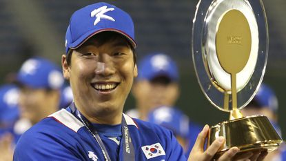 South Korea's Hyun-soo Kim holds the MVP award he received after beating the United States, 8-0, in the final game at the Premier12 world baseball tournament at Tokyo Dome in Tokyo, Saturday, Nov. 21, 2015.