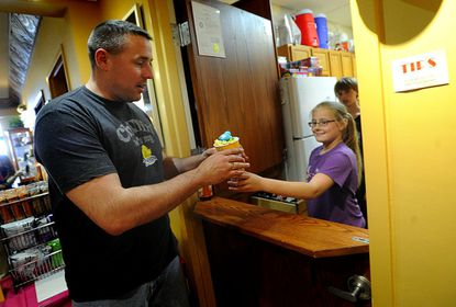 Lauren Mondor, 9, hands a Peep-topped popcorn to her father Rob Mondor as they work the concession counter at the Carroll Arts Center during the Carroll County Arts Council's annual PEEPshow Sunday.