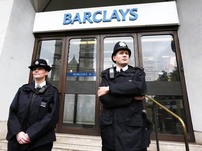 Police wait for protestors to appear at a branch of Barclays Bank in Westminster, central London.