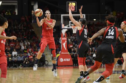 Washington Mystics forward Elena Delle Donne, left, jumps up to pass the ball as Las Vegas Aces guard Kelsey Plum (10) and guard Sugar Rodgers (14) defend during the first half of Game 2 of a WNBA playoff basketball series Thursday, Sept. 19, 2019, in Washington. (AP Photo/Nick Wass)