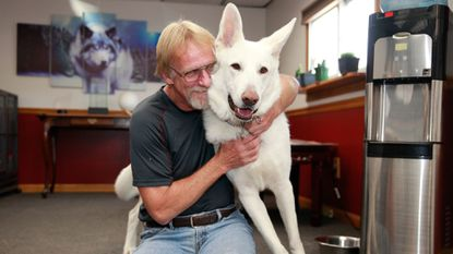 Gary Simmont, of Pasadena, hugs one of his rescued dogs, a German Shepherd named Samson. In March, Simmont donated a kidney to a fellow dog rescue volunteer named Laurel Weetall, of Germantown.