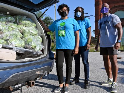 From left, Rachel Brooks, lead organizer, Genell Collins, operations manager, both with BUILD One Baltimore and Eric Skinner, site manager, with lettuce donated from City Seeds. They will deliver the produce to community members. August 5, 2020.