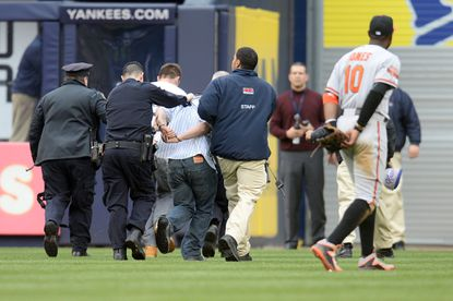 Adam Jones looks on as fans are escorted off by security after running on the field in the eighth inning Tuesday at Yankee Stadium.