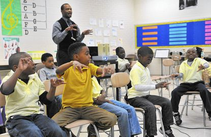 First-graders play imaginary instruments while music teacher Robert Bannister shows the class pictures of the musical instruments in an orchestra at Cecil Elementary School.