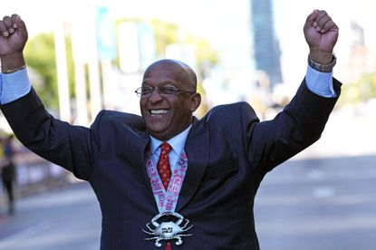 """Mayor Bernard C. """"Jack"""" Young raises his hands as he jokes with photographers and crosses the finish line of the Baltimore Marathon wearing a medal."""