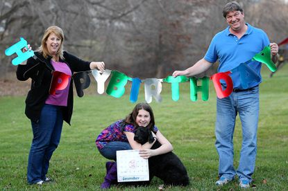 Dayna Crisco and her husband John pose for a photo with their daughter Leah and dog Elly at their home in Ellicott City. Leah will be turning 12 on 12-12-12.