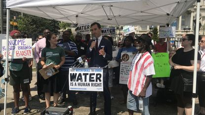 Councilman Zeke Cohen speaks at a protest against water rate increases in the city.