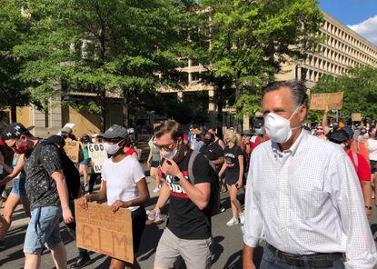 Sen. Mitt Romney (R-Utah) marches with a crowd singing Little Light of Mine in Washington D.C. on June 7.