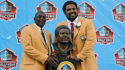 Jonathan Ogden, right, and his presenter Ozzie Newsome, left, pose with Ogden's Hall of Fame bust after his induction in 2018.