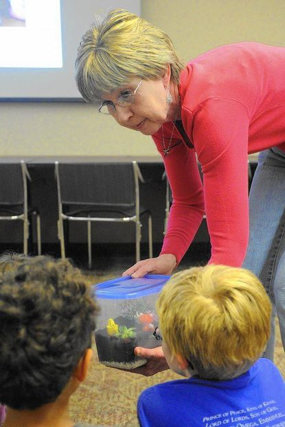 In this 2012 file photo, Mary Sadaka teaches children how to make terrariums at the Eldersburg branch of the Carroll County Public Library. A DIY Terrariums program will be held this Saturday, April 29 at 11 a.m. at the Taneytown branch.
