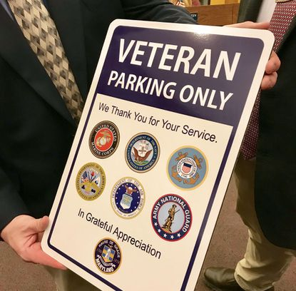 Havre de Grace Mayor William T. Martin holds one of the five signs that have been installed around the city designating parking spots for veterans only. Martin displayed this sign during the Nov. 4 City Council meeting.