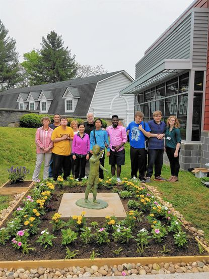 Linwood staff and students and Yumi Hogan with the new sculpture and garden at Linwood Center.