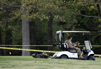 Investigators examine debris that fell on the Breton Bay Golf and Country Club after an Army Black Hawk helicopter crashed on April 17, 2017, in Leonardtown.
