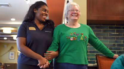 Shaniya Carroll, left, a resident assistant at Brightview Senior Living's Perry Hall location, celebrates with resident Mary Frances during the monthly birthday event.