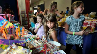 Left to right, Calley Slaton, 9, Natalia Vessali, 7, and Sabrina Vessali, 10, search through the 500 different candies to find what they want as they visit the Bulk Candy Store section of the Exhibition Hall during the Maryland State Fair.