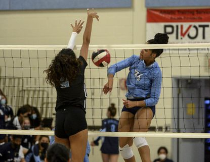 River Hill's Shreeni Chikyala gets a block against Howard's Tyller Williams in the first set. The visiting Howard Lions played the River Hill Hawks in girls high school volleyball Tuesday evening.