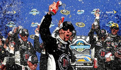 Kevin Harvick celebrates in victory lane after winning the NASCAR Sprint Cup Series CampingWorld.com 500 at Phoenix International Raceway on Sunday.