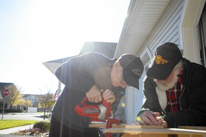 Ralph Reise, left, and Ken Vrtacnik, both of Westminste, work together to cut out the figure of a bear that will become part of the Carroll Lutheran Village's float on Nov. 11