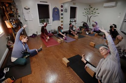 Instructor Stacey Swierzbinski, left, leads a yoga session at Branches of Yoga in Sykesville Thursday evening Jan. 23, 2020.