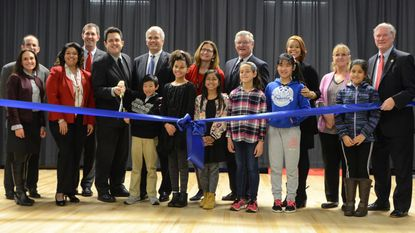 Baltimore County executive candidate Johnny Olszewski Jr., back row, second from left, joins a ribbon cutting at Padonia International Elementary in Cockeysville. The campaign of his opponent, Al Redmer, criticized Olszewski for attending the official county event as a candidate.