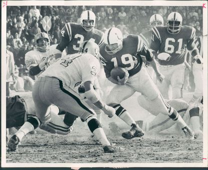 Johnny Unitas runs for it with Raiders' Gus Otto (No. 34) coming up to make stop on first quarter play.