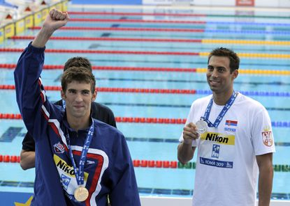 Michael Phelpsnext to Milorad Cavic after winning the 100-meterbutterfly at the FINA Swimming World Championships in Rome in 2009.