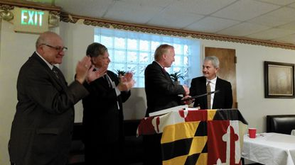 """Salvatore """"Mannie"""" Anello, left, and Arthur Frank applaud as Clem Kaikis, right, presents Maryland Comptroller Peter Franchot with a plaque designating him as an honorary knight in the Arbutus political club."""