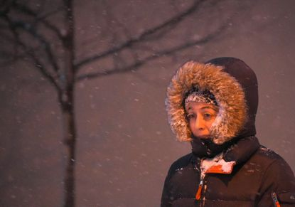 Jaclyn Grigoli of Federal Hill, Md., heads to a restaurant on Pratt Street in Baltimore on Friday as the snow begins to fall.
