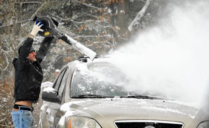 Roland Cross uses a snowblower to clear snow from his vehicle and driveway on Marley Station Road during the first snowfall of 2015.