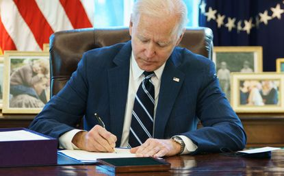 U.S. President Joe Biden signs the American Rescue Plan on March 11, 2021, in the Oval Office of the White House in Washington, D.C..