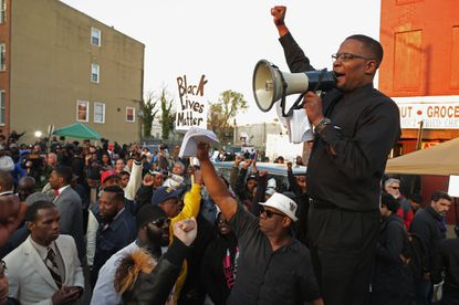 Attorney Malik Shabazz leads demonstrators during a protest against police brutality and the death of Freddie Gray outside the Western District station in the Sandtown neighborhood on April 22.