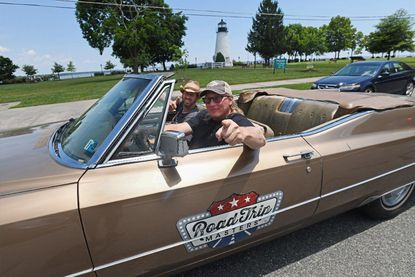 """""""Road Trip Masters"""" co-hosts Nick Kessler, center, and Brian Fulmer drive the show's 1968 Cadillac Deville Convertible past Havre de Grace's Concord Point Lighthouse. The show is featuring the city in one of its 10 episodes in season 3 and is in town filming for four days."""