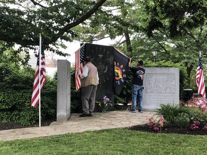 From left, Kevin Dayhoff and Walter Groomes place flags at the Carroll County Vietnam Veterans Memorial before a small, closed to the public prayer ceremony on Memorial Day.