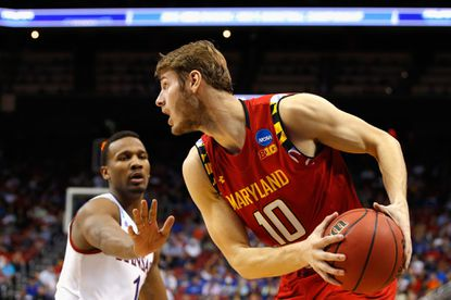 Jake Layman #10 of the Maryland Terrapins handles the ball against Wayne Selden Jr. #1 of the Kansas Jayhawks in the first half during the third round of the 2016 NCAA Men's Basketball Tournament at KFC YUM! Center on March 24, 2016 in Louisville, Kentucky.