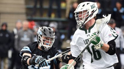 Johns Hopkins senior midfielder Joel Tinney, left, defending against Loyola Maryland on Feb. 17, had two goals and three assists in the No. 9 Blue Jays' 15-13 win at No. 10 Virginia on Saturday.
