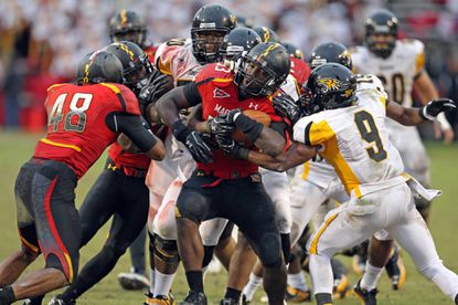 Maryland linebacker Lorne Goree, center, is tackled after intercepting a Towson pass in the second half.