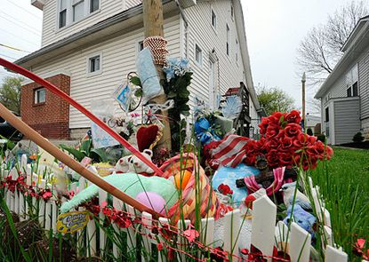 An informal memorial with stuffed animals and cards in front of Carl Lackl's home.