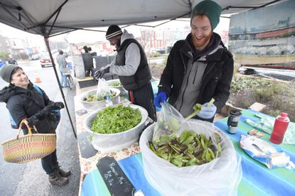 Matt Haines, right, and Tee Larkin with the Baltimore-based urban farming group Big City Farms fill an order of mixed greens for Hampden resident Brandy Iskin at the 32nd Street Farmers Market, open year round, in Baltimore on Saturday, Jan. 9.