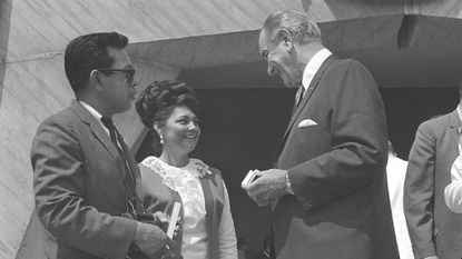 President Lyndon B. Johnson presents a souvenir pen to Mr. and Mrs. Lupe Arzola, Aug. 1, 1968, in Washington, during the signing of the Fair Housing Act outside the Department of Housing and Urban Development.