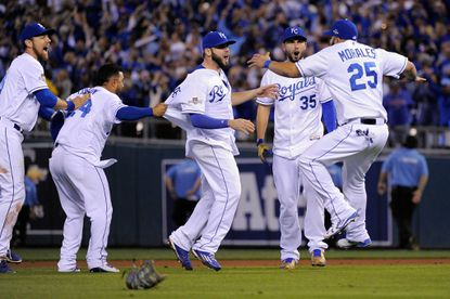 Mike Moustakas (8), Eric Hosmer (35) and Kendrys Morales (25) of the Kansas City Royals celebrate defeating the Houston Astros 7-2 in Game 5of the American League Divison Series at Kauffman Stadium on Oct. 14, 2015 in Kansas City, Mo.