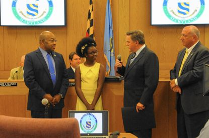 Jim Fielder, representing Gov. Larry Hogan's office, center, speaks to 12-year-old Grace Callwood as Harford County Council members Curtis Beulah, left, and Pat Vincenti, right, prepare to recognize her for her nonprofit work.