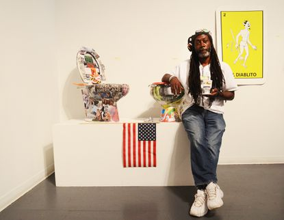 """Activist Duane """"Shorty"""" Davisposes with One of his toilets, 'America's Future with O'Malley' (left) which is currently on display at the Creative Alliance as part of itssalon-style exhibition, """"The Big Show,"""" alongside a toilet by activist Danielle Denise Beane Clayton titled, 'Tales From The Trenches' (right)."""